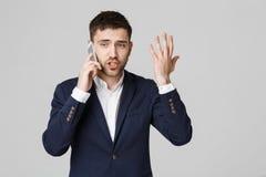企业概念-衣服的画象年轻英俊的恼怒的商人谈话在看照相机的电话 奶油被装载的饼干 免版税库存照片