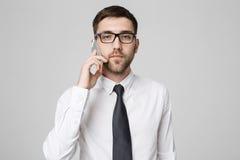 企业概念-衣服的画象年轻英俊的恼怒的商人谈话在看照相机的电话 奶油被装载的饼干 库存照片