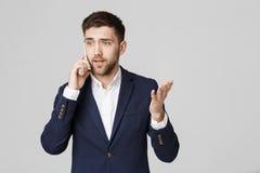企业概念-衣服的画象年轻英俊的恼怒的商人谈话在看照相机的电话 奶油被装载的饼干 库存图片