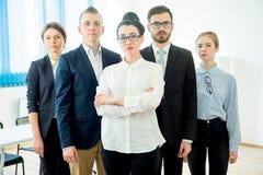 他们企业照相机不同的五名查找的成员纵向微笑的成功的小组 库存照片