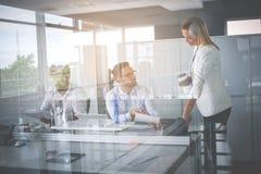 企业生意人服务台下来集中倾斜看起来中间办公室一人被安置的有选择性的三二whiteboard运作的文字 两个商人hav 图库摄影