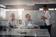 企业生意人服务台下来集中倾斜看起来中间办公室一人被安置的有选择性的三二whiteboard运作的文字 两个商人关于 免版税库存照片