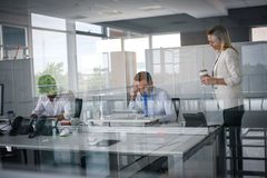 企业生意人服务台下来集中倾斜看起来中间办公室一人被安置的有选择性的三二whiteboard运作的文字 两个商人关于 库存照片