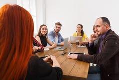 企业生意人cmputer服务台膝上型计算机会议微笑的联系与使用妇女 年轻队在现代办公室 库存图片