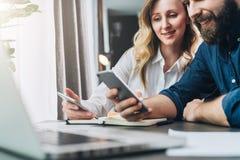 企业生意人cmputer服务台膝上型计算机会议微笑的联系与使用妇女 配合 坐在窗口和工作前面的桌上的微笑的女实业家和商人 图库摄影