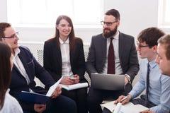 企业生意人cmputer服务台膝上型计算机会议微笑的联系与使用妇女 年轻愉快的商人男性和女性在现代办公室,在工作场所合作友好的讨论 库存照片
