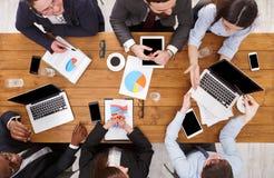企业生意人cmputer服务台膝上型计算机会议微笑的联系与使用妇女 不同种族的emploees队在办公室谈论工作,木桌顶视图的结果  免版税库存图片