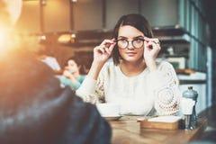 企业生意人cmputer服务台膝上型计算机会议微笑的联系与使用妇女 一个年轻女商人佩带的玻璃的画象,坐在咖啡馆在桌上 工作午餐,断裂 图库摄影