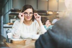 企业生意人cmputer服务台膝上型计算机会议微笑的联系与使用妇女 一个年轻女商人佩带的玻璃的画象,坐在咖啡馆在桌上 工作午餐,断裂 库存照片
