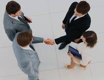 企业生意人cmputer服务台膝上型计算机会议微笑的联系与使用妇女 四个人顶视图站立接近彼此的formalwear的,当两他们握手时 图库摄影