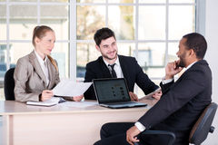 企业生意人cmputer服务台膝上型计算机会议微笑的联系与使用妇女 坐在Th的三个成功的商人 库存图片