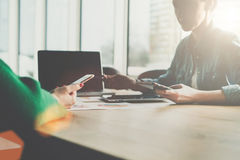 企业生意人cmputer服务台膝上型计算机会议微笑的联系与使用妇女 坐横跨从彼此的桌的两个年轻女商人,拿着智能手机,谈话,运作 免版税库存图片