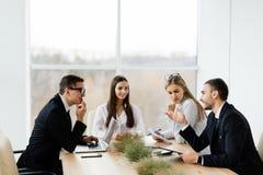 企业生意人cmputer服务台膝上型计算机会议微笑的联系与使用妇女 formalwear的谈论的商人某事,当一起坐在桌上时 库存图片