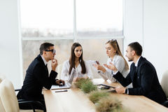 企业生意人cmputer服务台膝上型计算机会议微笑的联系与使用妇女 formalwear的谈论的商人某事,当一起坐在桌上时 图库摄影
