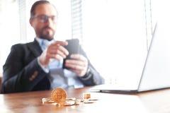 企业生活方式 贸易商在与膝上型计算机硬币的咖啡馆坐桌特写镜头被弄脏的浏览智能手机 图库摄影