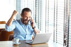 企业生活方式 贸易商在咖啡馆用咖啡和膝上型计算机对喜讯说对同事坐智能手机微笑 库存图片