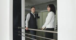 企业男性和中部年迈的妇女在一个现代办公室的大厅里站立并且谈话 股票录像