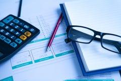 企业笔、计算器和玻璃在财政图 免版税库存照片