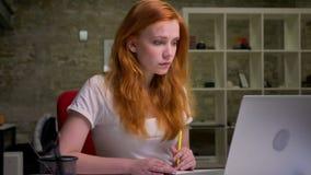 企业红发妇女在办公室努力工作并且书写在她的笔记本,当坐在膝上型计算机附近,令人愉快时 影视素材