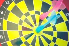 企业营销和战略概念:蓝色箭的关闭击中了在飞镖的目标在葡萄酒过滤器作用 免版税库存图片