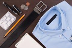 企业衬衣偶然成套装备和辅助部件传送带有笔的和口香糖在木桌上 免版税库存图片