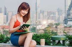 企业计算器概念货币 亚裔女商人是读和writeing书 女实业家使用他们头脑和记录 免版税库存图片