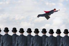 企业进展概念超级英雄在天空的商人飞行 库存图片