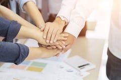 企业配合小组人手,有堆积的朋友挤作一团,显示团结和配合 免版税库存图片