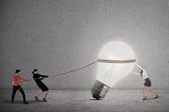 企业配合拉扯电灯泡 库存图片