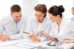 企业队与片剂个人计算机一起使用在办公室 图库摄影