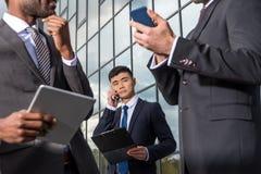 企业队会议和使用智能手机和数字式片剂户外在办公楼附近 免版税库存图片