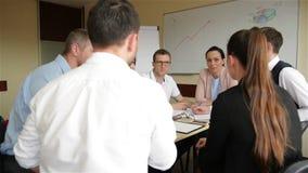 企业队的概念在运作的过程的 年轻专家与新市场项目一起使用 项目负责人见面 股票视频