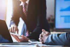 企业队礼物 年轻商人有会议和工作在现代办公室 膝上型计算机、片剂和文件在工作 免版税库存图片