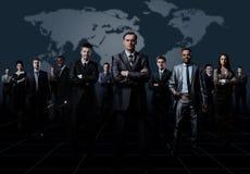 企业队站立在黑暗的背景的形成了年轻商人 免版税库存图片