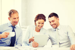 企业队获得与片剂个人计算机的乐趣在办公室 免版税库存图片