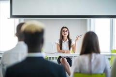 企业队训练听的会议概念 美丽的女商人发表演讲关于会议 免版税库存照片