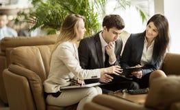 企业队谈论工作证明书坐长沙发在一个现代办公室的大厅 免版税库存照片