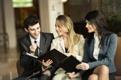 企业队谈论工作证明书坐长沙发在一个现代办公室的大厅 免版税库存图片