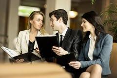 企业队谈论工作证明书坐长沙发在一个现代办公室的大厅 库存图片