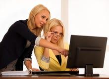 企业队-工作检查数据库的两名妇女在办公室 免版税库存图片