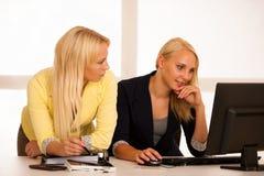 企业队-工作检查数据库的两名妇女在办公室 免版税库存照片