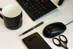 企业静物画:键盘、老鼠、笔、剪刀、计算器和杯子 免版税库存照片