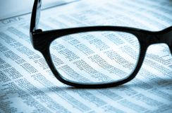 企业财政报纸报告把玻璃透镜,商人的工作场所进行下去 免版税库存图片