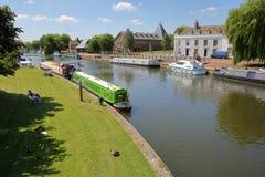 伊利,英国- 2017年5月26日:河沿在有被停泊的驳船的春天在Great Ouse河和传统房子 图库摄影