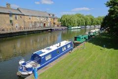 伊利,英国- 2017年5月26日:河沿在有被停泊的驳船的春天在Great Ouse河和传统房子 免版税库存图片