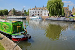 伊利,英国- 2017年5月26日:河沿在有被停泊的驳船的春天在Great Ouse河和传统房子 免版税图库摄影