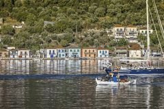 伊塔卡Vathi港口 enterring港口的希腊渔夫` s小船 免版税库存照片
