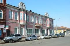 伊尔库次克,俄罗斯, 2017年3月, 16日 在卡尔・马克思街道上的汽车在伊尔库次克在春天,房子41 前革命建筑学 免版税库存图片