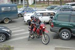 伊尔库次克,俄罗斯-, 18 2015年:在汽车之间的摩托车在城市街道上在伊尔库次克 图库摄影