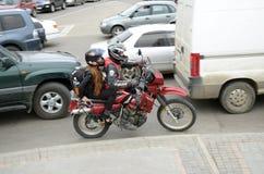伊尔库次克,俄罗斯-, 18 2015年:在汽车之间的摩托车在城市街道上在伊尔库次克 免版税图库摄影